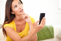Young woman wondering while holding a cell phone Stock Photography