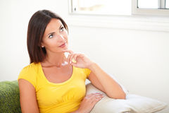 Young woman wondering while touching her chin Royalty Free Stock Image