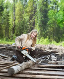 The young woman in wood saws a tree a chain saw.Portrait in a sunny day Royalty Free Stock Photo