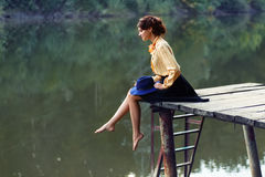 Young woman on wooden bridge. Side view of dreaming girl sitting on jetty forest and river on background. Beautiful woman sitting by the lake. Lonely woman Stock Photography