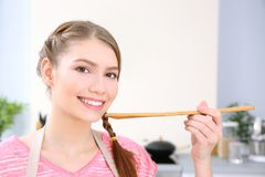 Young woman with wooden spoon. At home Stock Photos