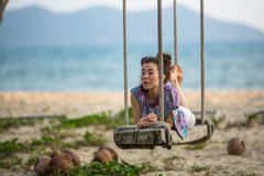 Young woman on the wooden swings on sea beach. Young mixed race woman on the wooden swings on sea beach Royalty Free Stock Photo