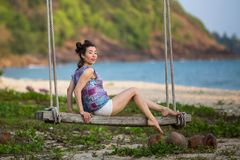 Young woman on the wooden swings on sea beach. Young mixed race woman on the wooden swings on sea beach Stock Photo