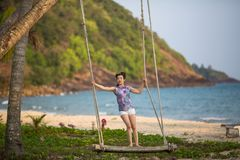 Young woman on the wooden swings on sea beach. Young mixed race woman on the wooden swings on sea beach Stock Images