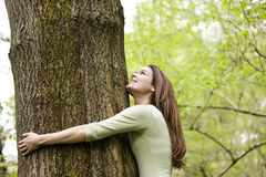 A young woman in woodland hugging a tree and looking up Stock Photo