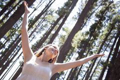 Young woman in woods feeling freedom Stock Image