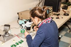 Young female electronic technician at work.