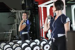 Young  woman work out in fitness. Young healthy woman work out in fitness club with dumbbelss Stock Photography