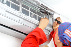 Young woman worker adjusting air conditioner system Royalty Free Stock Photos
