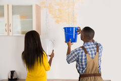 Young Woman And Worker Collecting Water In Bucket From Ceiling Royalty Free Stock Photos
