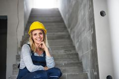 Young woman worker with a yellow helmet sitting on the stairs on the construction site. Copy space stock image