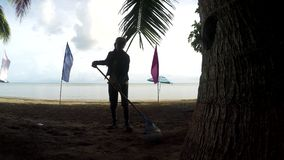 Young woman working as a beach cleaner raking litters, debris on tropical sandy beach. Lucena City, Quezon, Philippines - June 4, 2018: Young woman working as a stock video footage