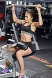Young woman working the back. Young woman working at the lat pulldown machine in the gym Stock Photography