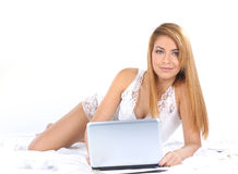 A young woman is working in the bed on a laptop Royalty Free Stock Photos