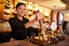 A young woman working behind a bar looking to camera, horizontal Stock Photography