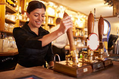 A young woman working behind a bar preparing drinks Stock Image