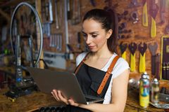 Young woman working in a bicycle repair shop Royalty Free Stock Image