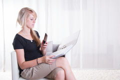 Young woman working with binder on her knees Stock Photo