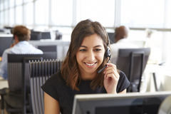 Young woman working in a call centre, holding headset Royalty Free Stock Photography