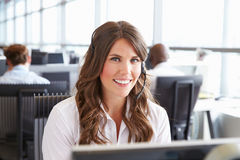 Young woman working in a call centre, looking to camera Stock Photo