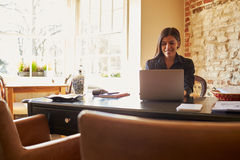 Young woman working at the check-in desk of a boutique hotel Royalty Free Stock Images