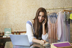 Young woman working in clothing store on phone, front view Stock Images