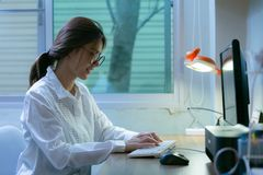 Young woman working on co-working home at night. royalty free stock image