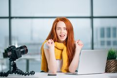 Young woman working on computer with cameras and accessories on table. Royalty Free Stock Photos