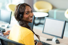 Young woman working on computer with headset Royalty Free Stock Photos