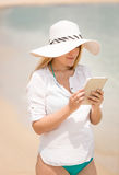 Young woman working on digital tablet at beach at windy day Royalty Free Stock Photo