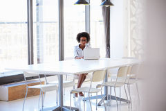 Young woman working in empty meeting room Stock Photo