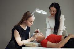 Young woman working on eyelash extensions. Young women working on eyelash extensions. Woman Eye with Long Eyelashes Royalty Free Stock Photos