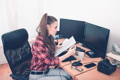 Young woman working at her desk with desktop computer and documents royalty free stock photography