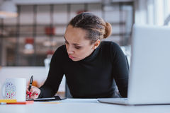 Young woman working at her desk Royalty Free Stock Photos