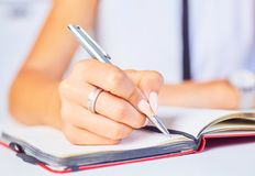 Young woman working at her desk taking notes closeup. Focus on hand writing on a notepad. stock image