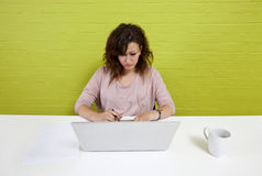 Young woman working at her laptop on a clean desk Royalty Free Stock Photography