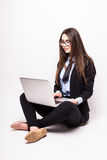 Young woman working on her laptop, sitting on the floor Stock Photo