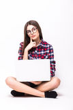 Young woman working on her laptop, sitting on the floor over sparse Royalty Free Stock Photos