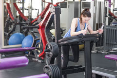 Young woman working her quads at machine press in the gym Royalty Free Stock Photography