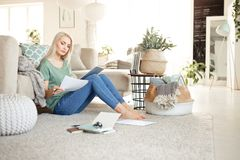 Young woman working at home, sitting on floor in living room stock photo