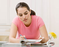 Young woman working on homework Royalty Free Stock Images
