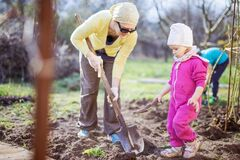 Free Young Woman Working In Garden While Her Little Daughter Playing With Spade Beside Her Royalty Free Stock Photography - 180731127