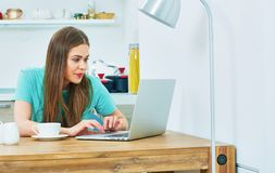 Young woman working in kitchen with laptop. Stock Photos