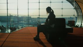 Young woman working with laptop in airport terminal. Waiting for my flight. Silhouette against the background of a large. Silhouette of young woman working with stock video