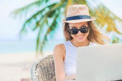 Young woman working in laptop on the beach. Freelance work. Young attractive woman in sunglasses and dress with hat working in laptop on the beach. Girl Royalty Free Stock Image