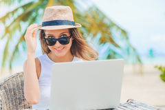 Young woman working in laptop on the beach. Freelance work. Young attractive woman in sunglasses and dress with hat working in laptop on the beach. Girl Stock Photography