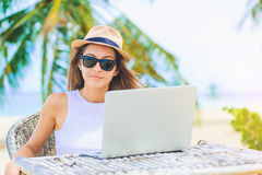 Young woman working in laptop on the beach. Freelance work. Young attractive woman in sunglasses and dress with hat working in laptop on the beach. Girl Royalty Free Stock Photo