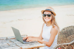 Young woman working in laptop on the beach. Freelance work. Young woman in dress with hat working in laptop on the beach. Girl Freelancer working Royalty Free Stock Photo
