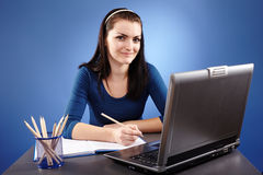 Young woman working with laptop on blue background Stock Image