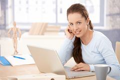 Young woman working on laptop in bright office Stock Photo